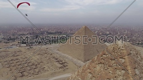 Aerial shot showing parachuting near to The Great Pyramids of Giza by day