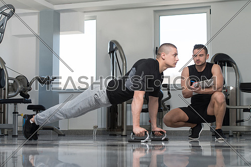 Personal Trainer Showing Young Man How To xercise Push-Up Strength In A Health And Fitness Concept