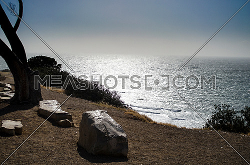 A silhouette image by the ocean from a cliff, water in a silver color