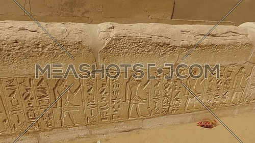 Reveal shot for small pharaonic temple in Saqqara Area showing paintings on wall at day.