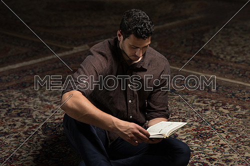 Adult Muslim Man Is Reading The Koran In The Mosque