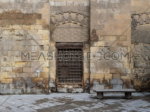 Wooden window with decorated iron grid over stone bricks wall and marble garden bench, Moez Street, Cairo, Egypt