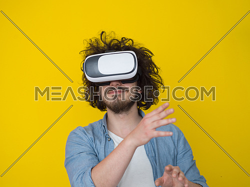 Happy man getting experience using VR headset glasses of virtual reality, isolated on yellow background