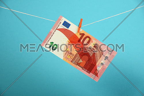 European economy crisis, decline of Euro, ten Euro banknote with red arrow down hanged descending with pin at rope over blue background