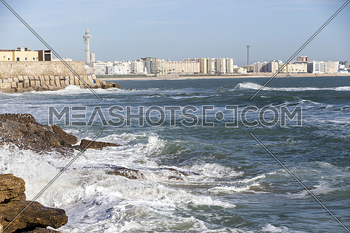 Waves hit the rocks on the promenade of the La Caleta beach in Cadiz, Spain