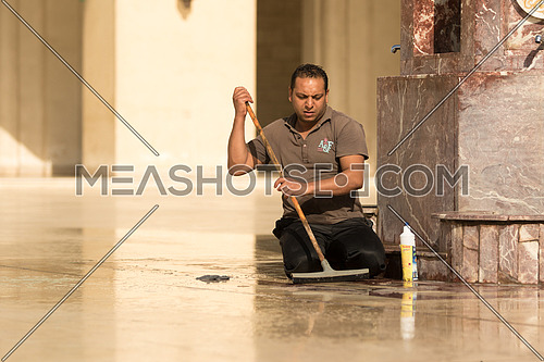 A janitor is cleaning the marble floor of Al-Hakim mosque in Al-Moez street, old Cairo