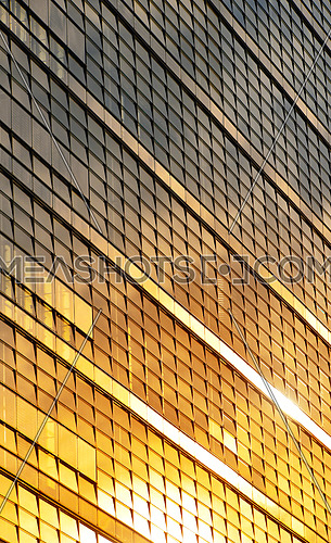 Orange colored glass windows of modern business office building at sunset in evening, diagonal perspective, low angle view