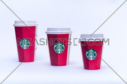 Starbucks takeaway paper cup, in special design for Christmas in different sizes on a white background; December 2018 - Cairo, Egypt.
