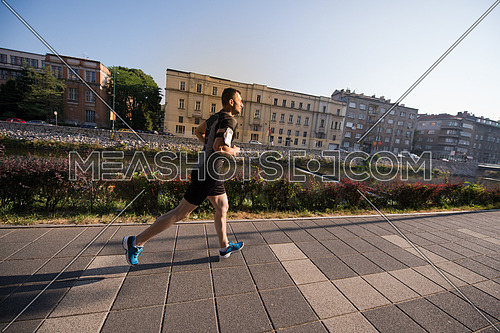 young sporty man jogging at sunny morning in the city