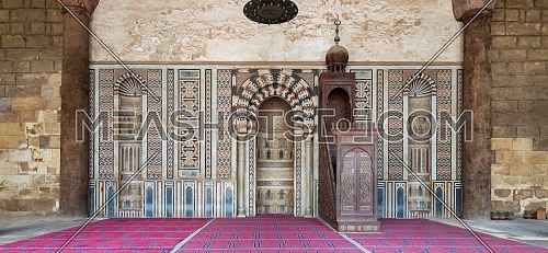 Colorful decorated marble wall with engraved Mihrab (niche) and wooden Minbar (Platform) at the Mosque of Al Nasir Mohammad Ibn Qalawun, situated in the Citadel of Cairo in Egypt