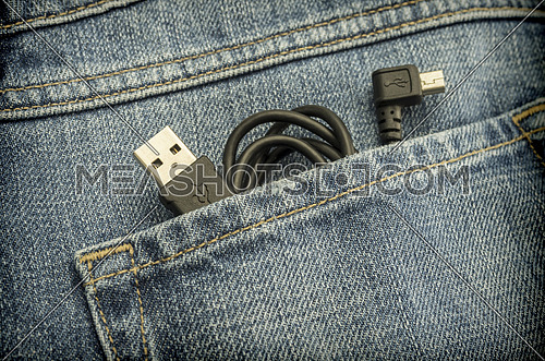 Cable usb inside pocket of jeans, conceptual image