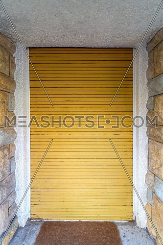 Background of bricks stone wall and closed yellow roll-up door
