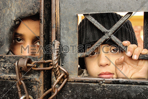 Two Syrian children standing in front of a school gate for refugees in Cairo Egypt