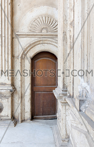 Wooden ornate door over white marble decorated wall. One of the entrances of the Mosque of Muhammad Ali Pasha (Alabaster Mosque), Citadel of Cairo, Egypt