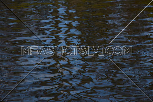 Colorful blue ripples and waves running on water surface texture background