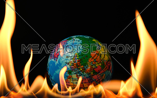 Close up earth globe in flames as symbol of world on fire, danger, political, economic crisis or pandemic