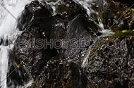 Waterfall slow stream, water over the rocks and stones in watercourse of river or brook, close up