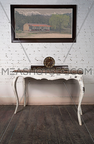 Vintage still life of an old retro desktop clock placed on a white vintage wooden table on background of white painted brick wall