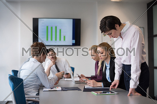 young businesswoman in casual hipster clothes working on tablet computer at modern startup business office, people group working and brainstorming in background