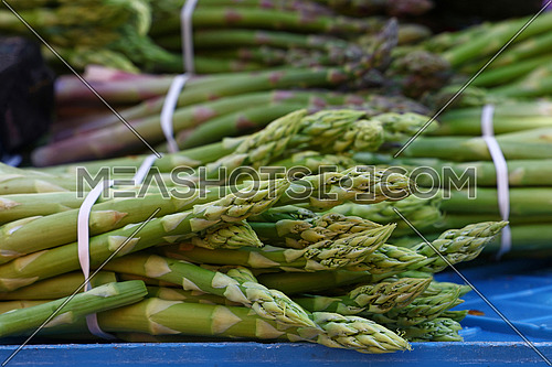 Bunch of fresh green asparagus shoots at retail market display, close up, high angle view