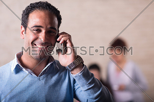 Young casual middle eastern businessman talking on the phone in modern stylish office with smile