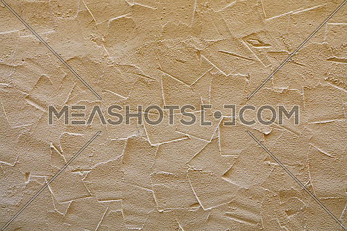 Rough brown beige wall surface of decorative embossed painted lime plaster background texture, close up