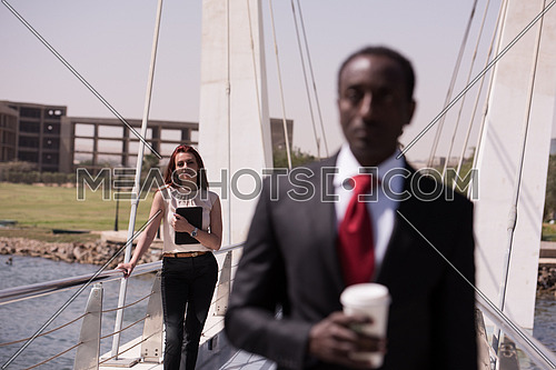 young business woman working on tablet computer at modern bridge business in motion concept afro american businessman blured in front