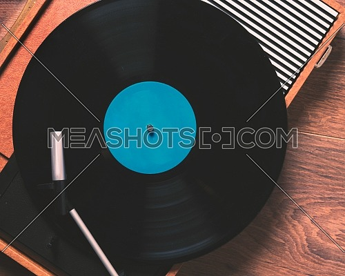 Older Gramophone with a vinyl record on wooden table, top view close up,vintage style.
