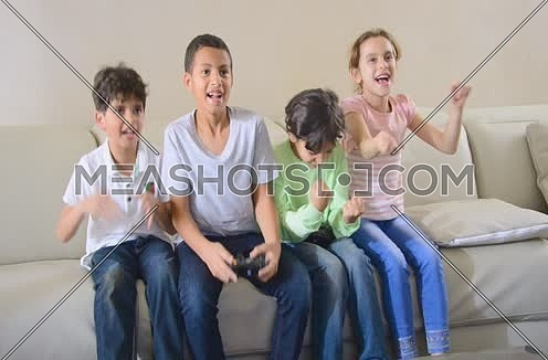 kids playing video games using joy sticks and game console