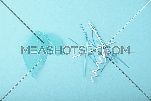 Blue skeleton leaves and paper cuts, stripes and spirals over design paper background