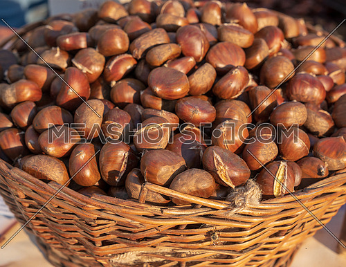 Fresh chestnuts in the basket,sold at the market,sunny day.