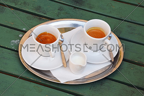 Close up one silver metal tray with white cups of espresso coffee on saucers with spoons and milk jug served on green painted wooden table, elevated high angle view