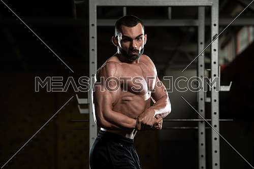 Portrait Of A Young Physically Fit Man Performing Side Chest Pose - Muscular Athletic Bodybuilder Fitness Model Posing After Exercises