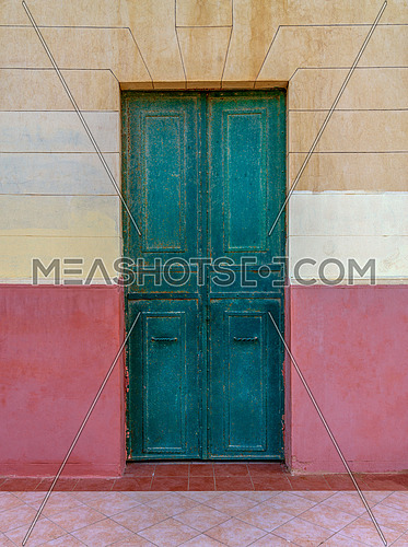Old grunge green wooden door in an old wall painted in beige and red, Montaza Public Park, Alexandria, Egypt