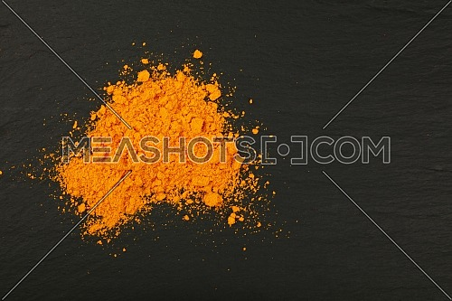 Close up one heap of yellow turmeric powder spice on background of black slate board, elevated top view, directly above