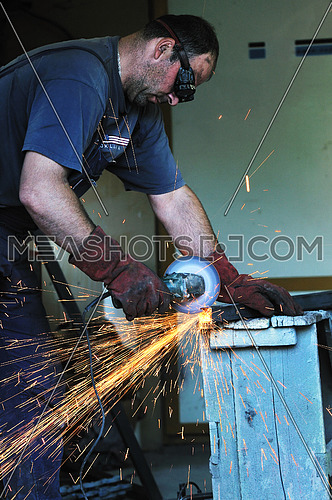 industry worker cut steel with spinning machine and spark