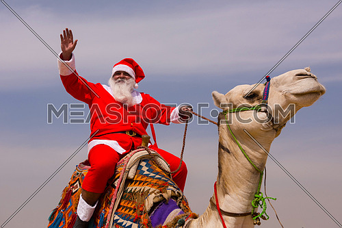santa claus riding a camel in pyramids desert in Egypt Christmas concept