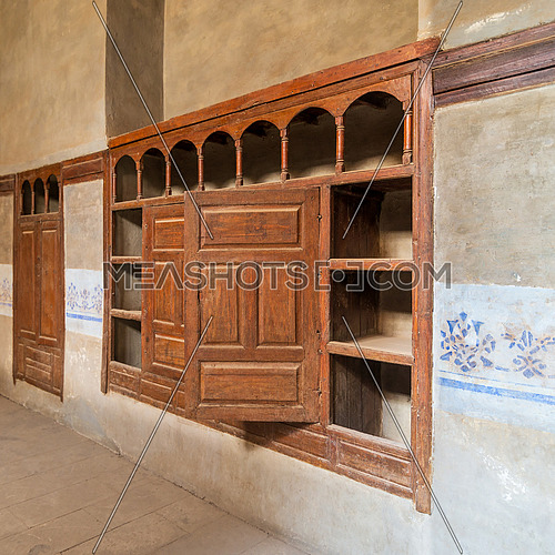 Wooden arabesque ottoman era cupboard with engraved decorations embedded in a grunge wall
