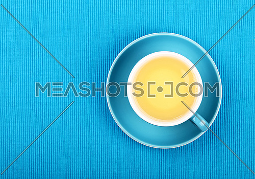Full cup of clear green tea on blue saucer over green blue tablecloth, close up, elevated top view