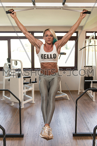 Middle Aged Woman Performing Hanging Leg Raises Exercise - One Of The Most Effective Ab Exercises