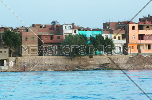 Long shot for Country side houses beside river Nile