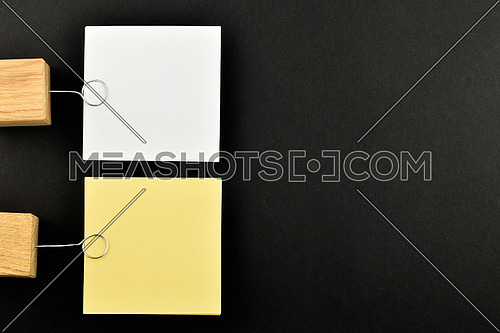 List, Two paper notes, white and yellow, with wooden holders isolated on black paper background for presentation