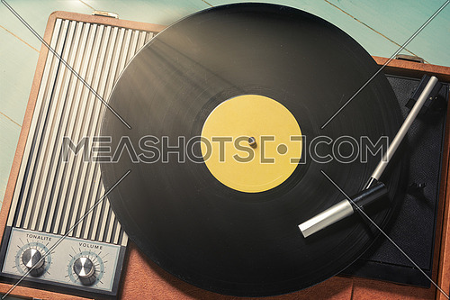 Vintage turntable with a vinyl record on green wooden table, top view and copy space.