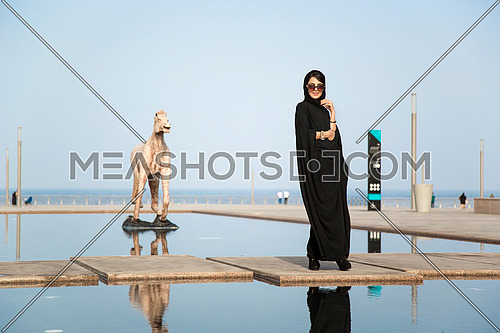 Saudi Lady wearing black abaya by the sea and an Horse statue at day.