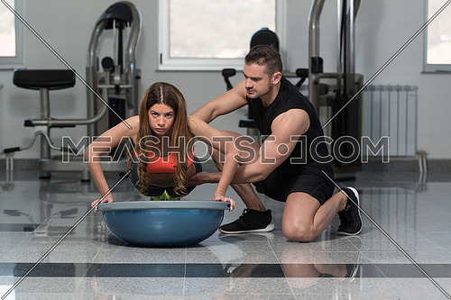 Personal Trainer Showing Young Woman How To Train On Bosu Push Ups In A Health And Fitness Concept