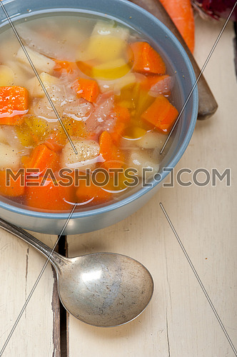 Traditional Italian minestrone soup on a rustic table with ingredients