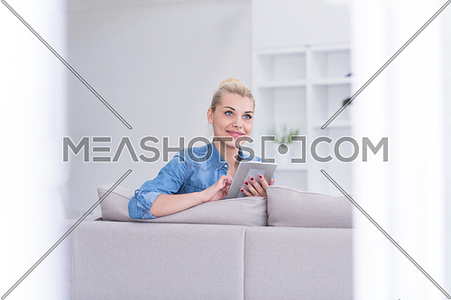 young happy woman on sofa using tablet computer at luxury home