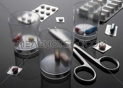 Dosage glasses medication next to scissors, conceptual image, horizontal composition