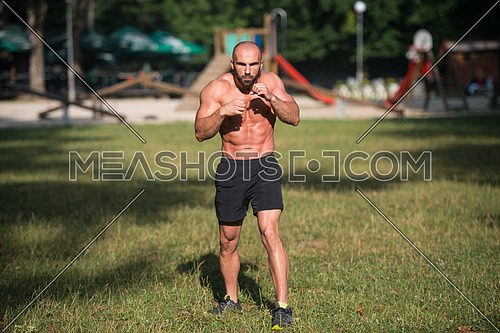 Adult Muscular Sports Guy With A Naked Torso Is Boxing - Doing Street Workout Exercises In Park
