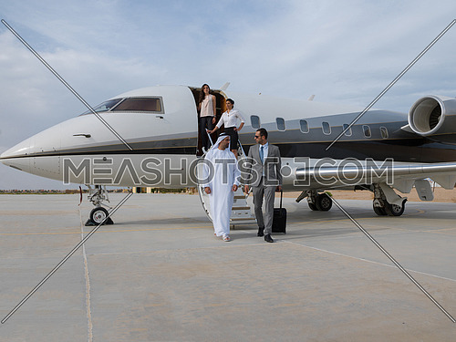 young successful businessman walking with his Arab business partner in front of private airplane carrying a suitcase